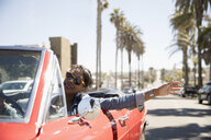 Carefree woman driving convertible with arms outstretched on sunny California road - HEROF23793