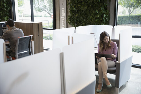 Businesswoman working with digital tablet in cubby in coworking space - HEROF23844