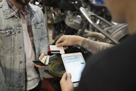Customer paying motorcycle mechanic with credit card reader and digital tablet in auto repair shop - HEROF23865