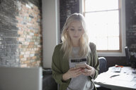Creative businesswoman texting with smart phone in office - HEROF23907