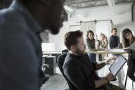 Creative businessman using digital tablet in meeting - HEROF23925