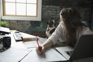 Female architect working, looking over shoulder at dog in office - HEROF23937