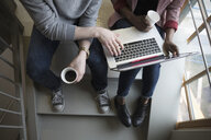 Creative businessman and businesswoman using laptop and drinking coffee in stairwell - HEROF23946