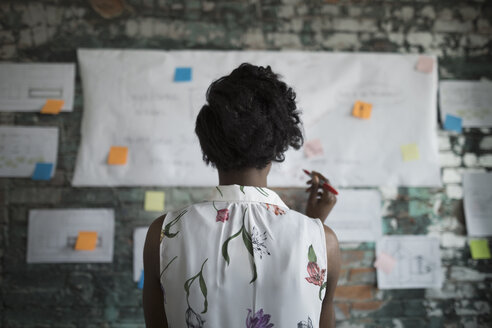Creative businesswoman brainstorming, reviewing flow chart hanging on brick wall in office - HEROF23994