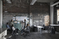 Creative business people brainstorming at brick wall in open plan loft office - HEROF24003