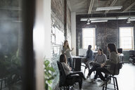 Creative business people brainstorming at brick wall in open plan loft office - HEROF24006