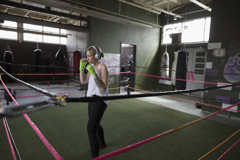 Female boxer listening to music with headphones, shadow boxing in boxing ring at gym - HEROF24027
