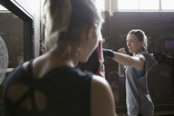 Female boxers training at punching bag in gritty gym - HEROF24036