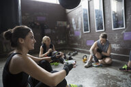 Female boxers resting, eating snack post workout at gritty gym with punching bags - HEROF24039