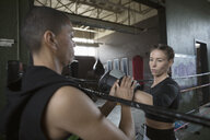 Female boxer training woman wearing boxing glove in boxing ring - HEROF24042