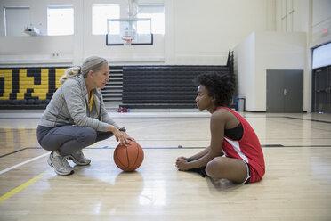 Female coach coaching basketball player in college gymnasium - HEROF24081