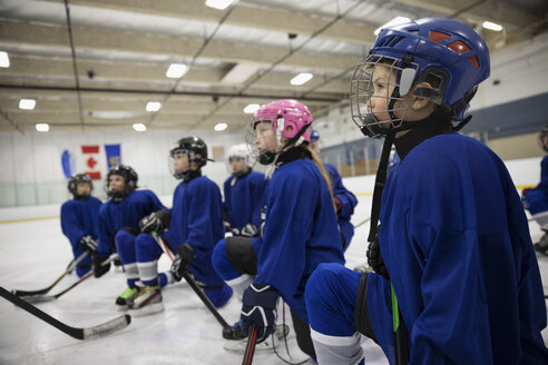 Attentive boy and girl ice hockey players listening on ice hockey rink - HEROF24105