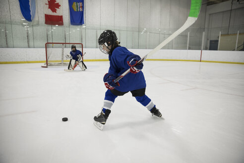 Boy ice hockey player taking a shot at goal on ice hockey rink - HEROF24108