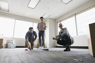 Business people with tape measure measuring floor space in new office - HEROF24138