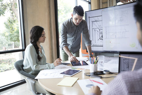 Architects reviewing digital blueprints in conference room meeting - HEROF24207