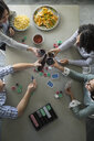 Overhead view of friends toasting and playing poker - HEROF24315