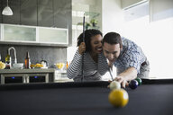 Playful couple playing pool - HEROF24318