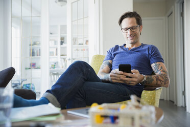 Relaxed man with tattoos texting in living room - HEROF24342