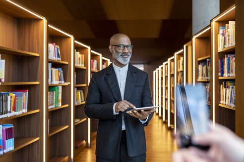 Portrait of smiling businessman with digital tablet at library - FMKF05353