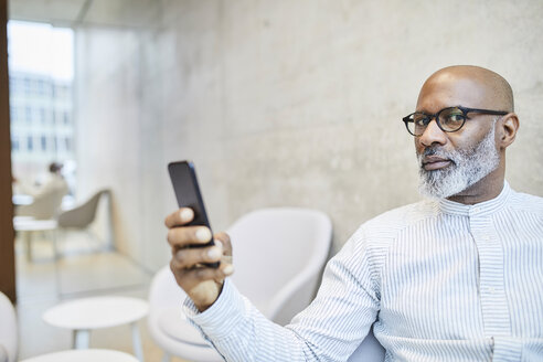 Portrait of bald mature businessman with cell phone - FMKF05356