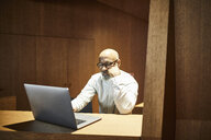 Portrait of mature man working on laptop at workspace with wood panelling - FMKF05359
