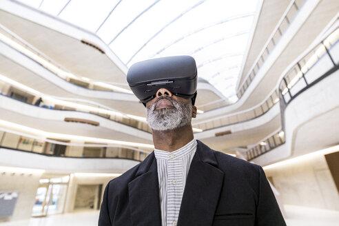Bearded businessman using Virtual Reality Glasses - FMKF05371