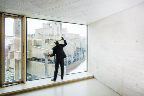 Back view of barefoot businessman with Virtual Reality Glasses standing on window sill looking out of window - FMKF05377
