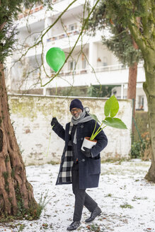 Smiling mature man with green balloon and potted plant in winter - FMKF05389