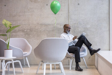 Mature businessman with green balloon sitting on armchair using digital tablet - FMKF05392