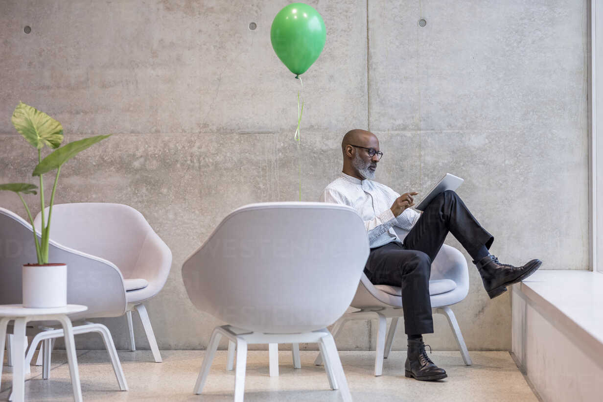 Mature businessman with green balloon sitting on armchair using digital tablet - FMKF05392 - Jo Kirchherr/Westend61