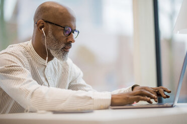Mature businessman with earphones working on laptop - FMKF05395