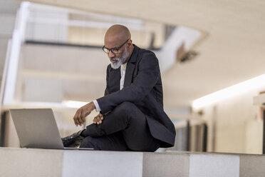 Bald mature businessman looking at laptop thinking - FMKF05398