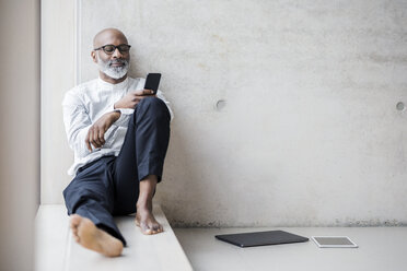 Barefoot mature businessman sitting on window sill looking at smartphone - FMKF05404