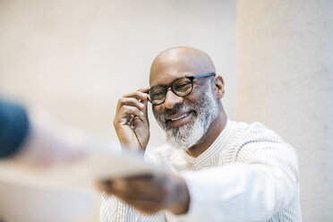 Portrait of smiling businessman with glasses - FMKF05410