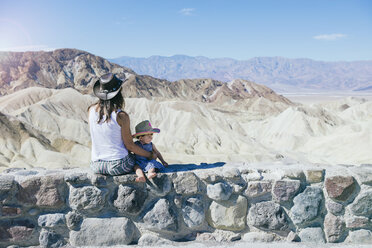 USA, California, Death Valley National Park, Twenty Mule Team Canyon, mother and baby girl sitting on wall - GEMF02847