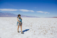 USA, California, Death Valley National Park, Badwater Basin, happy mother walking with baby girl in salt basin - GEMF02856