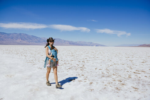 Mother and baby in a baby carrier traveling in Badwater Basin, a salty basin and the lowest point in North America, Death Valley National Park, California and Nevada, United States - GEMF02856
