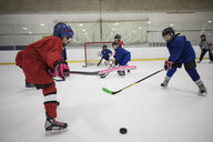 Girl ice hockey player taking a shot on ice hockey rink - HEROF24371
