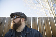 Hipster man with beard and flat cap looking away at wood fence - HEROF24377