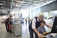 Grandfather and grandson at interactive exhibit in war museum hangar - HEROF24404