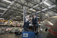 Grandfather and grandson looking at airplane in war museum hangar - HEROF24407