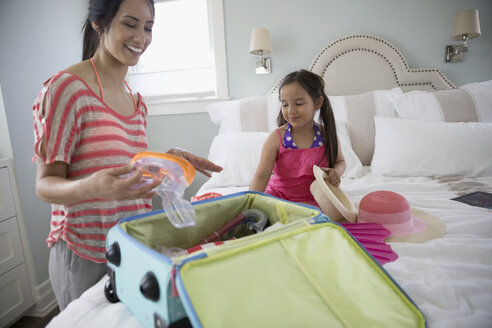Mother and daughter packing for vacation on bed - HEROF24437