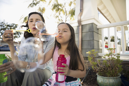 Grandmother and granddaughter blowing bubbles on summer porch - HEROF24443