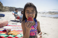 Latina girl eating watermelon on sunny beach - HEROF24470