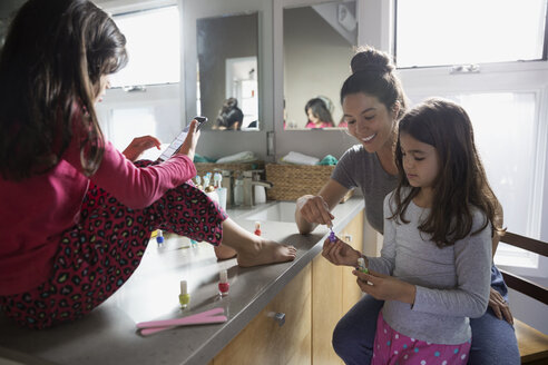 Mother giving daughter pedicure on bathroom counter - HEROF24485