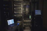 Laptop and server panels in dark server room - HEROF24500