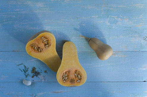 Whole and sliced butternut squash, garlic clove and herbs on light blue wood - ASF06302