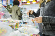 Midsection of girl filling candies in plastic while buying at shop - ASTF02842
