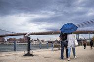 People walking on footpath by East River against Brooklyn bridge during storm - ASTF02845