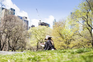 Woman sitting on grass against trees and buildings at Central Park - ASTF02863